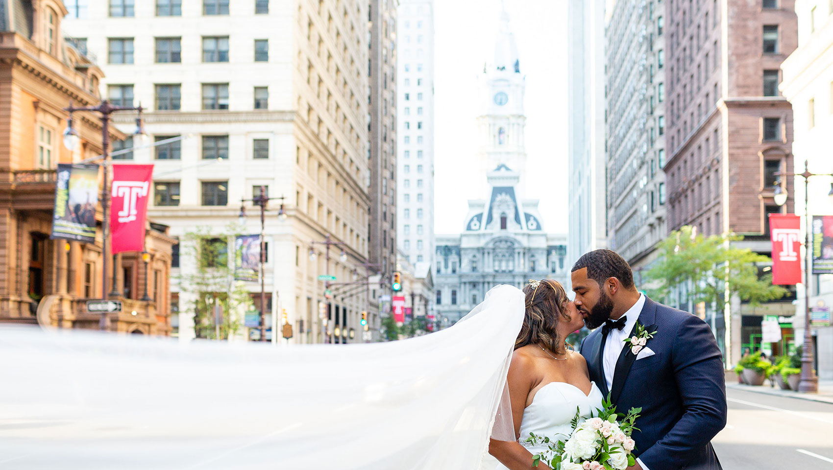 Bride and groom kissing on Broad Street in front of Philadelphia's city hall building