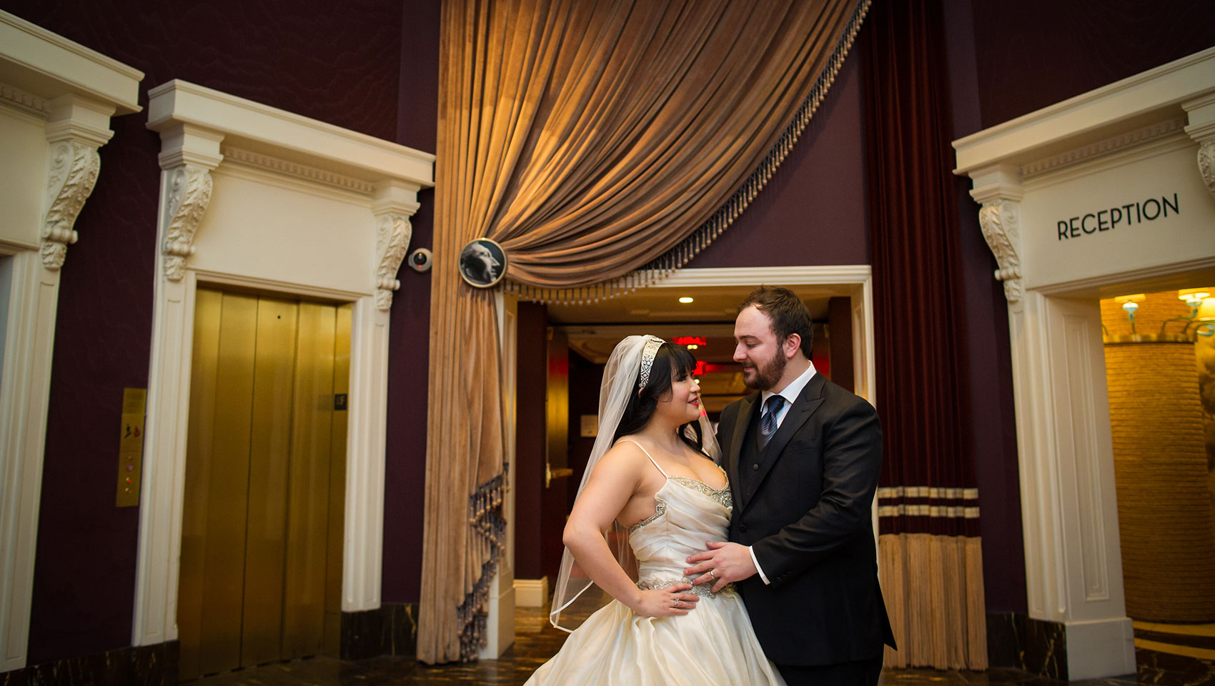 Bride and groom looking at each other in Kimpton Hotel Monaco Philadelphia's lobby