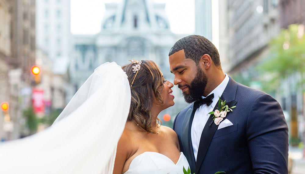 Bride and groom kissing in front of Philadelphia's City Hall building exterior