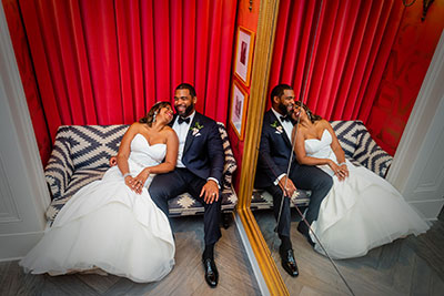Bride and groom sitting next to each other on accent chair at Kimpton Hotel Monaco Philadelphia