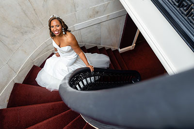 Bride in wedding dress walking up staircase