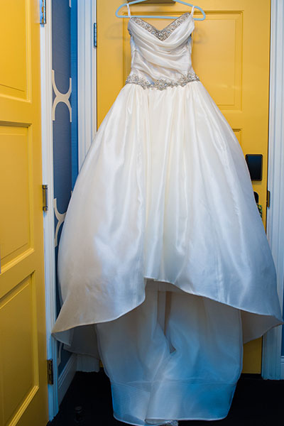 Bridal wedding dress hanging on door