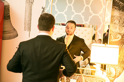 Groom in suit looking at himself in mirror