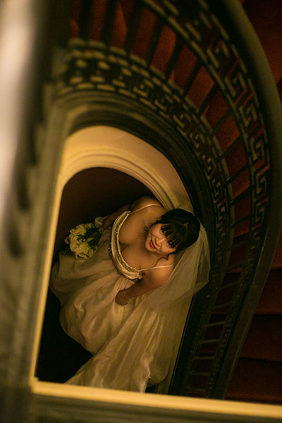 Bride looking up from the center of spiral staircase