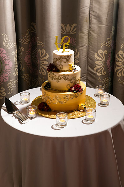 Tiered wedding cake with candles on table